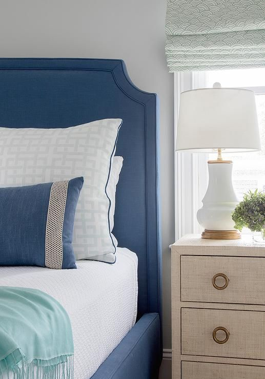 A cream nightstand lit by a white gourd lamp sits beneath a window dressed in a light blue roman shade and beside a blue upholstered bed accented with white bedding topped with a peacock blue throw blanket and a blue pillow layered in front of a white and blue sham.
