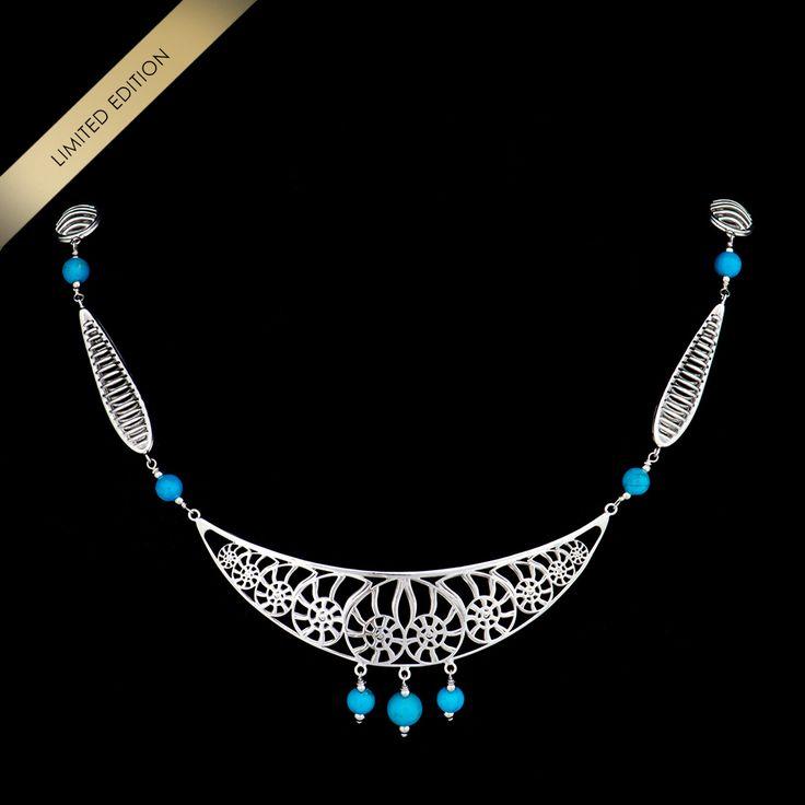 I riflessi lunari dell'argento rodiato e il turchese delle sfere creano una dolce armonia con il particolare design del sorriso di conchiglie. Un gioiello che rappresenta tutta l'eleganza e la femminile sensualità della donna Konk