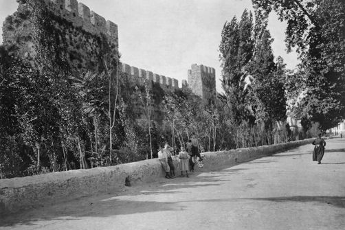 Pedestrians on a street near massive crenelated stone fortress walls 1910s  Location: Antalya, Asia Minor.  Photographer: ERNEST LLOYD HARRIS/National Geographic Creative