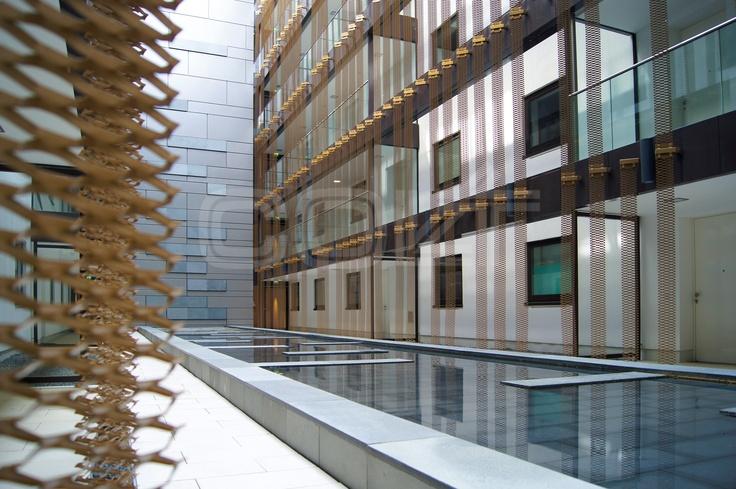 Automatische Rauchschürzen im Kranhaus Nord in Köln. Wie Architektur gewordene Botschafter der Zukunft ragen die drei Kranhäuser im Kölner Rheinauhafen aus der Bebauung der Altstadt hinaus. Die 18 Stockwerke hohen Gebäude mit der Form eines auf den Kopf gestellten großen L, die an die utopischen Wolkenbügel von El Lissitzki erinnern. Automatische Rauchschürzen von Colt bieten optimalen passiven Brandschutz.