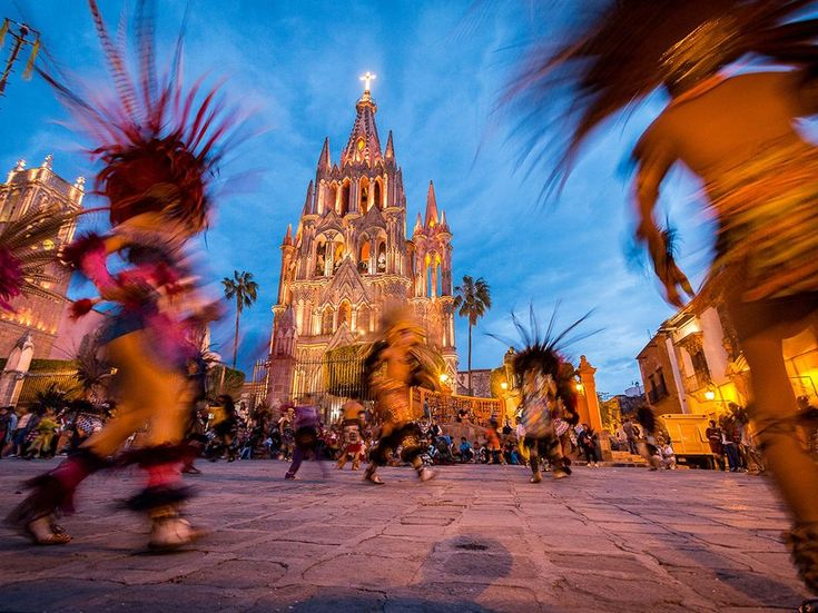 Picture of a celebratory dance in front of Parroquia de San Miguel Arcangel, Mexico.