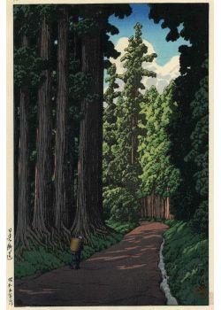 日光街道 昭和5年(1930)作 「日光への街道。杉の夏木立が鬱蒼として生い茂った道を、かごを背負った老婆が向うへあるいている、山中の閑かな景趣を写したたての構図である。今朝もまたギラギラ輝く日照りで、午後の雨雷を約束する積雲を遠空にみせ、昼なお暗いばかりに近景の高どを落して、右側から光線をあてた趣向である。巴水の作品でもいやみのない佳作となっている。」