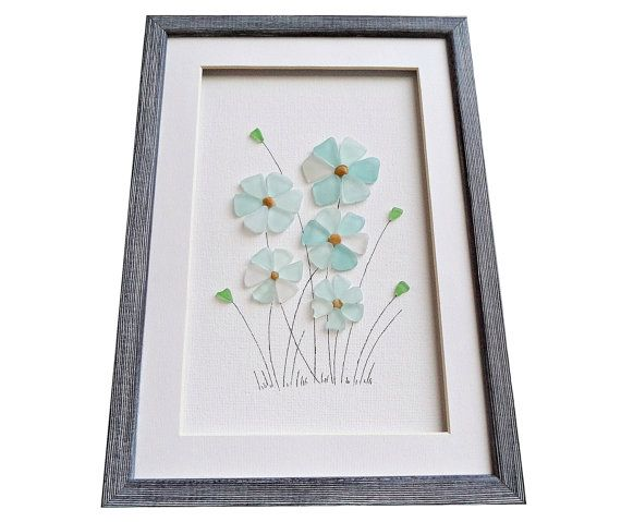 Unique framed sea glass art made of genuine beach glass. These beautiful flowers are a great idea for a new home housewarming gift. This wall art could be that special piece that adds color and feeling to that bleak spot in your home that needs a change. The colors of sea glass are turquoise, aqua, sea foam and green. All materials are hand-collected by me from the beautiful beaches around my hometown Varna, Black Sea coast. Size: 20 cm x 28 cm / approx 8 x 11 /  Framed with a white matting…