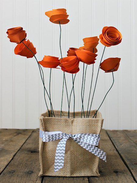 Pretty Paper Flower Centerpiece  The idea, no bow different color container, other kinds of flowers can work too