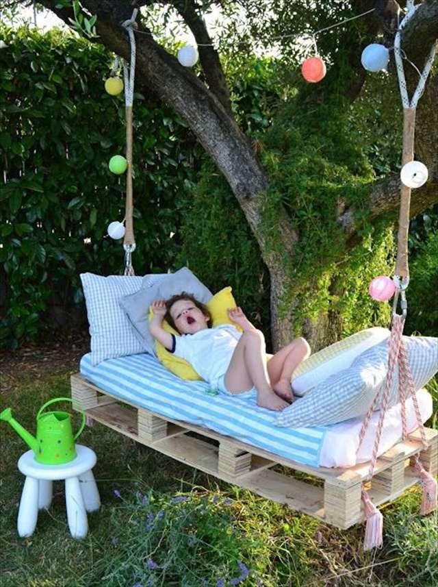 lit enfant en palettes en bois, suspendu par une branche d'arbre dans le jardin