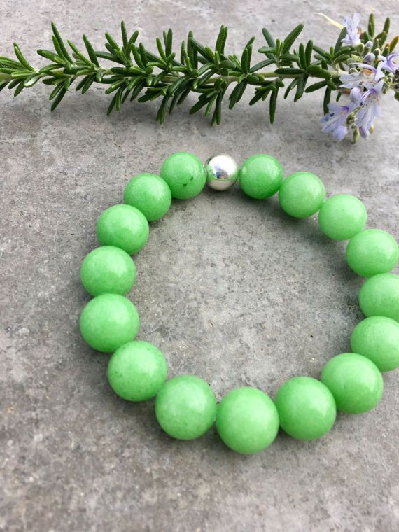 ♥︎ Dyed Jade Bracelet. Pantone Color of the Year Bracelet. St. Pattys Day Bracelet. Womens Beaded Bracelet. Mothers Day Gift. Jade Jewelry. Womens Bracelet. Studio BB Designs ♥︎ This beaded bracelet is made with 12mm dyed jade beads in the Pantone color of the year! A beautiful shade of green. Perfect for St. Pattys Day, or everyday wear! It is hand strung on heavy elastic cord with a sterling silver ball to hide the knot. This item is one-of-a-kind and truly breathtaking! Only one…