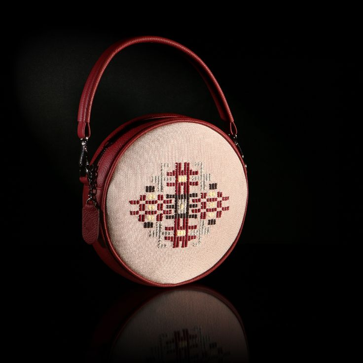 "The handmade woven round bag ""Iris"" adorns a pattern inspired of a traditional female outfit of Thrace. The color of the leather is deep red and the background is in pink silk weaving"
