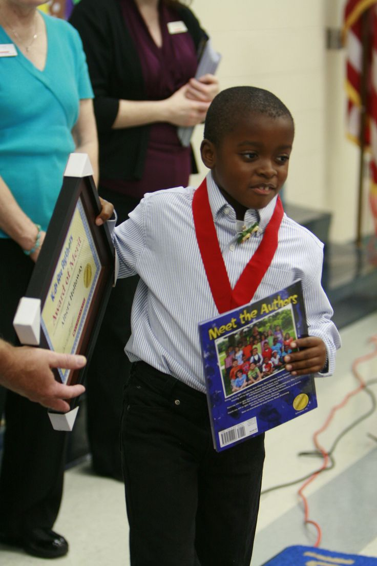 A young author receives his published book and a medal for ...