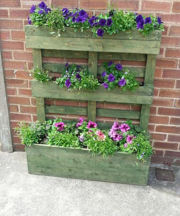 jardiniere palette repeinte en vert pastel, bac a fleur et dossier, des fleurs couleur mauve et rose, mur en briques