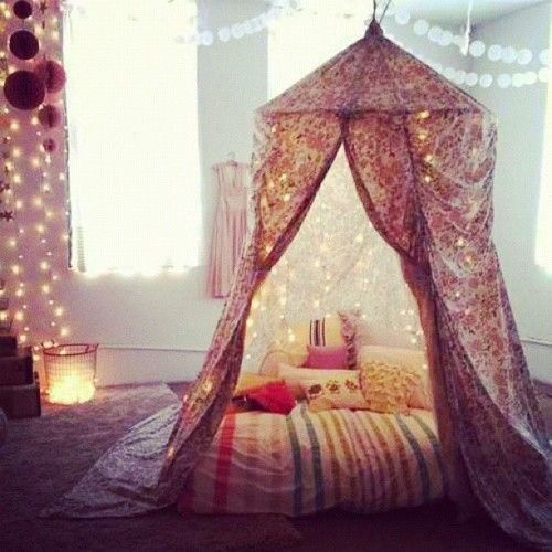 Soft lights, DIY canopy, throw pillows. This would be so nice as a hang out space to read, watch tv, take a nap. So nice!