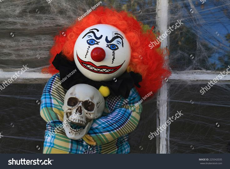 Typical Halloween Decorative Doll of Scary, Creepy, Character dolls Clown Killer in front of old house window cover by spider web.