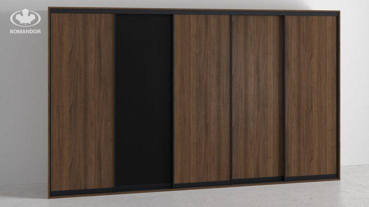 Bardzo pojemna szafa Komandor z drzwiami przesuwnym. Mebel na zdjęciu posiada fronty z ramkami w systemie Szafir w kolorze anody grafitowej, wypełnienie frontu to piękny, orzechowy fornir. Korpus szafy wykonany został z płyty laminowanej, zbliżonej kolorem do forniru użytego na froncie. Ciekawym akcentem w drzwiach szafy jest zastosowanie jednego skrzydła z czarnego matowego akrylu.