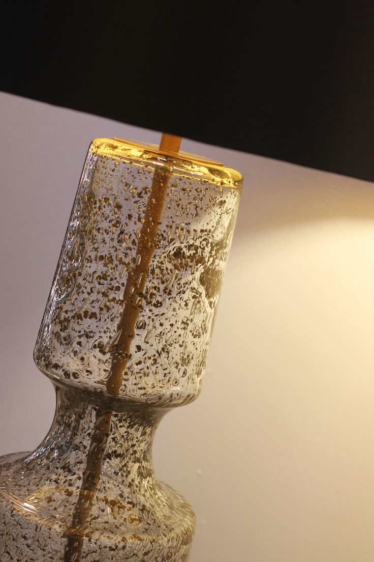 The Antero glass table lamp features a beautifully sculpted form with a concave mid-section and intricate bubble detailing. The range is available in three colours; the elegant and subtle 'Antique', the warm 'Amber Smoke', and the vivid and striking 'Teal. All colour finishes are perfectly complemented by the Antique Brass metalwork.