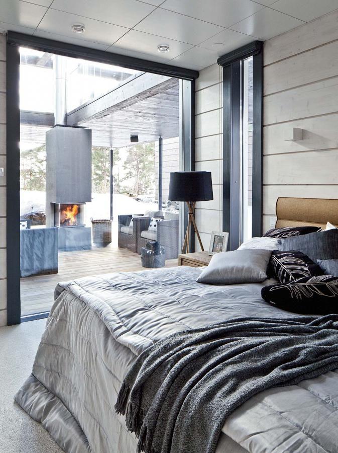 Makuuhuoneessa on lattiasta kattoon ulottuva ikkuna, josta näkee terassille. Päiväpeitto, huopa ja tyynyt Luhta Homen mallistosta. Jalkavalaisin ja yöpöytä Jackpointilta. | Moderni kotisatama | Koti ja keittiö