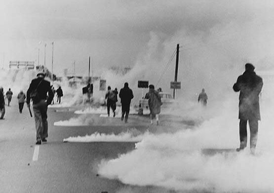 """Alabama state troopers wear gas masks as tear gas is fired on marchers in 1965. Fifty years ago, about 600 people began a 50-mile march from Selma, Alabama, to the state capital of Montgomery so that they could protest discriminatory practices that prevented black people from voting. But as the marchers descended to the foot of the Edward Pettus Bridge, state troopers used brutal force and tear gas to push them back. The event is now known as """"Bloody Sunday."""""""
