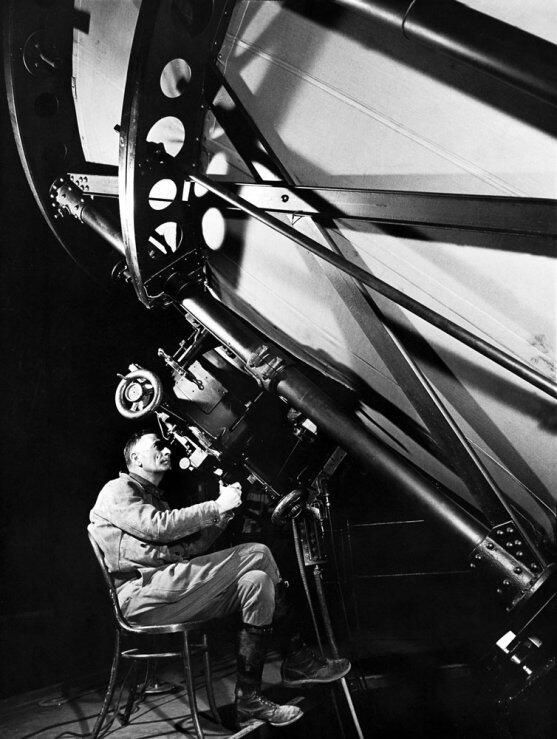 Astronomer Edwin Hubble peers though the eyepiece of the 100-inch Hooker telescope at Mt. Wilson Observatory, 1937
