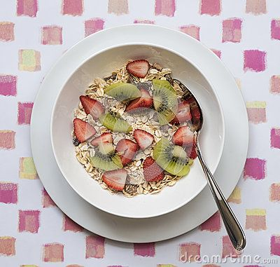 A white bowl of multi grain breakfast cereal and spoon topped with slices of strawberries and kiwi fruit on a patterned placemat.