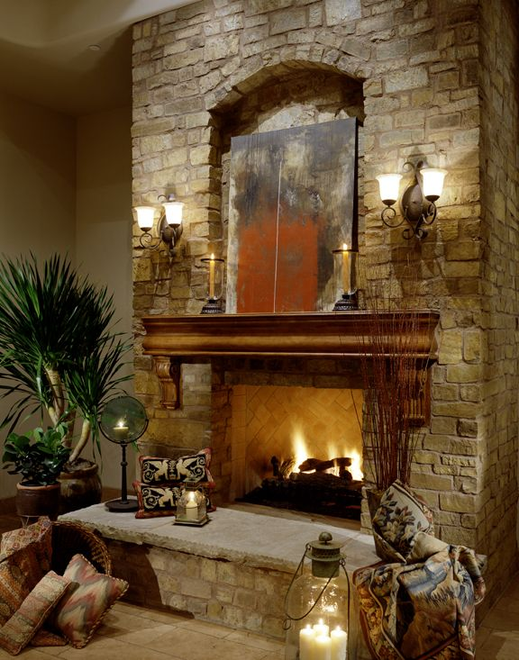 This elegant fireplace is unique in that it has two sconces mounted above the mantel. The home decor around the fireplace adds sophistication while the throw pillows add comfort.