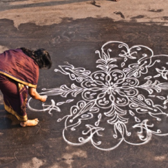 """please read: Kolam is a form of sand painting that is drawn using rice powder by female members of the family in front of their home. It is widely practiced by Hindus in South India. A kolam is a sort of painted prayer - a line drawing composed of curved loops, drawn around a grid pattern of dots. Kolams are thought to bestow prosperity to homes."""
