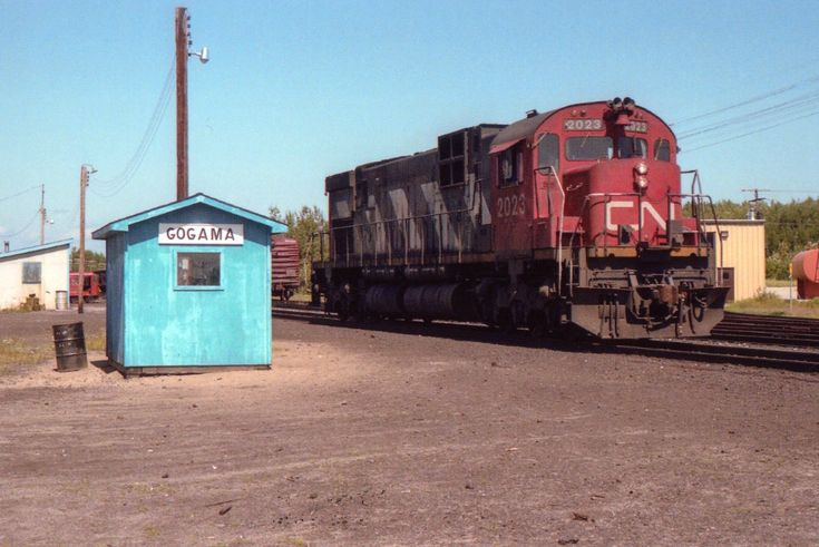"""CN 2023, playing the roll of """"yard switcher"""", rolls to a stop by the VIA Shack after working a cut of cars at the north end of the yard in the community of Gogama. This community was little known by anyone outside of the hunting and fishing crowd until two nasty CN oil train derailments occurred within a few miles of this location earlier this year. But for me it was another one of those places to visit, just to see what was there. It was still a stop for VIA, due to its remoteness; but…"""