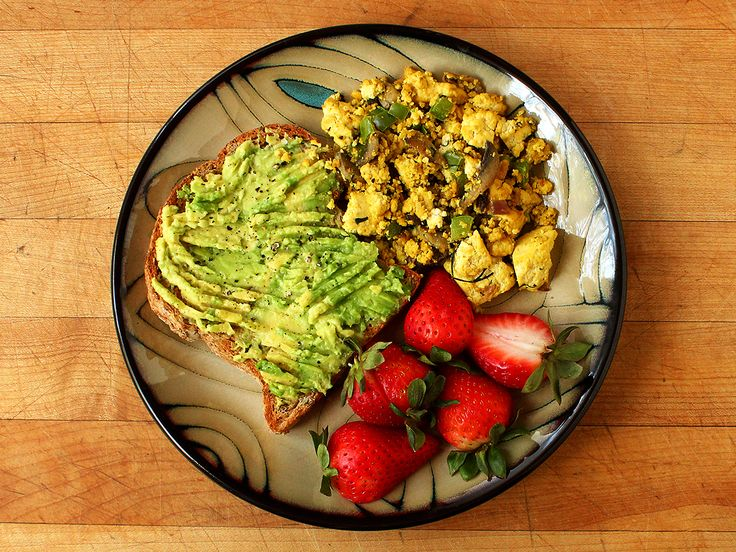 Sprouted grain toast with mashed avocado, salt, and pepper. Scrambled tofu with mushrooms and green pepper (extra-firm tofu, mushrooms, green pepper, garlic, onion, nutritional yeast, turmeric, cumin, and coconut oil) and halved strawberries. http://garden-of-vegan.tumblr.com/