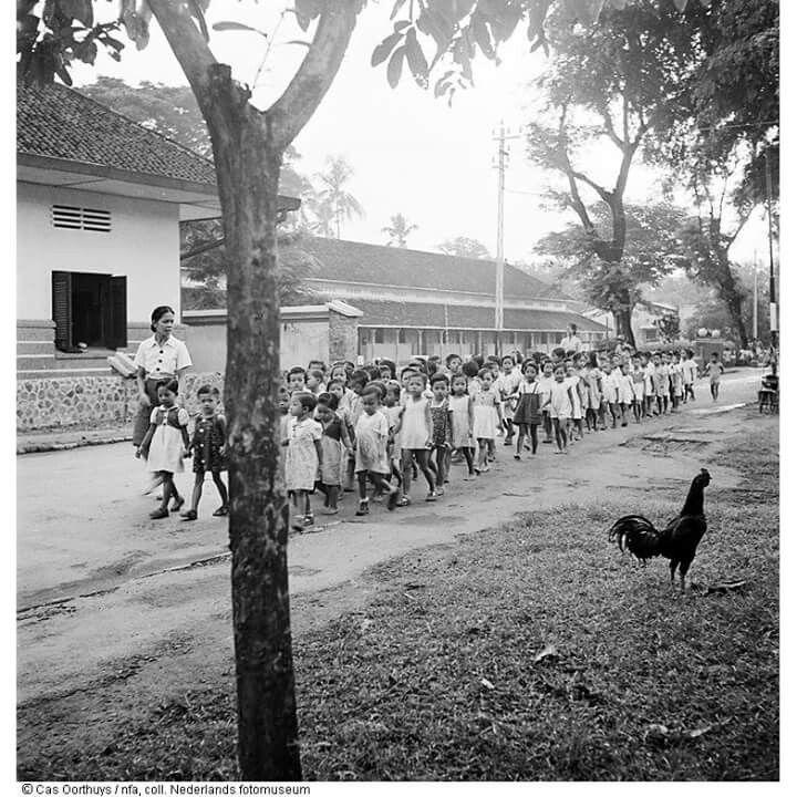 Guru membimbing murid di jalan (1947)