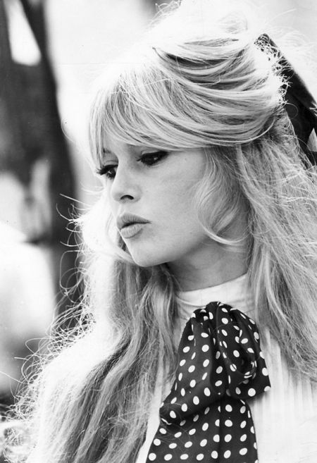 Brigitte Bardot in her made-famous hairstyle and bow! Although she does usually go for classic whites and blacks, patterns do make their way into her wardrobe! #styleicon #modcloth