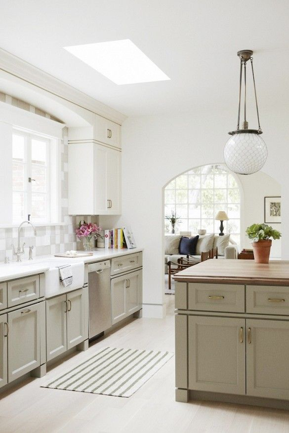 Neutral kitchen with retro chandelier and tiled backsplash: