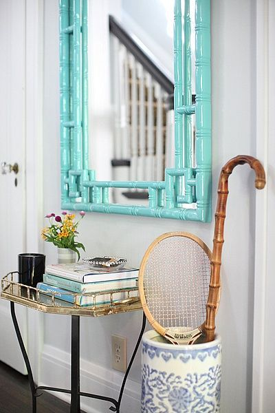 Pretty little foyer with umbrella stand and turquoise bamboo mirror.
