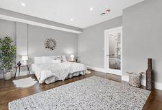 Weiche graue Wände schaffen eine dramatische Kulisse für dieses geräumiges Schlafzimmer.