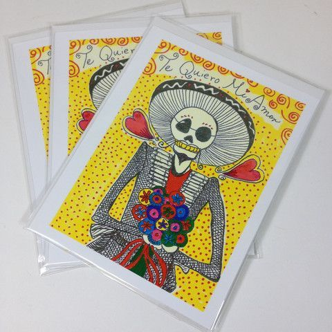 """A handmade card on white paper and decorated with a catrina with a large sombrero holding a bouquet of flowers. Blank inside. Comes with a white envelope. She is saying, """"Te Quiero Mi Amor."""" Translation: """"I love you my love."""" 7 available state of origin: California dimensions: 4"""" by 6"""""""