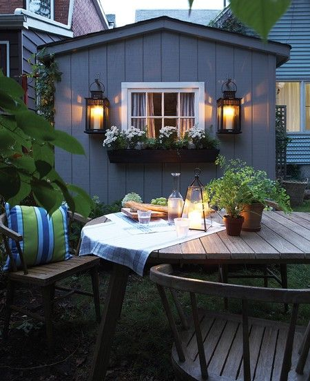Stagecoach style lanterns + flower-box under window + outdoor dining table