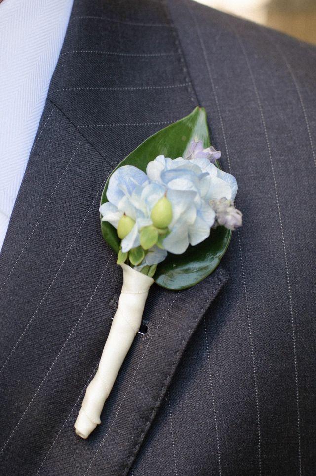 Ojal de la boda hortensias azul apoyó con una hoja verde, y estaba envuelto en cinta de raso blanco para que coincida ramo de Lee.