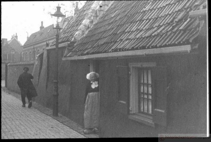 Vrouw in Zwolse klederdracht in deuropening huis aan de Grote Baan of Kleine Baan in de Kamperpoort, ca. 1930 #Overijssel #Salland