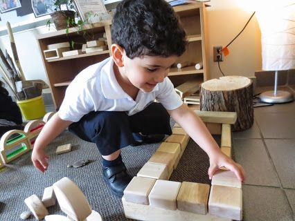 Our PK friend tries to balance blocks to make walls for his house, all with a smile on his face.