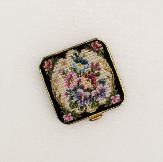 Heres a classic compact from the 1950s, with a floral petit point lid in shades of lilac, orchid, rose, and blue on a cream background, surrounded