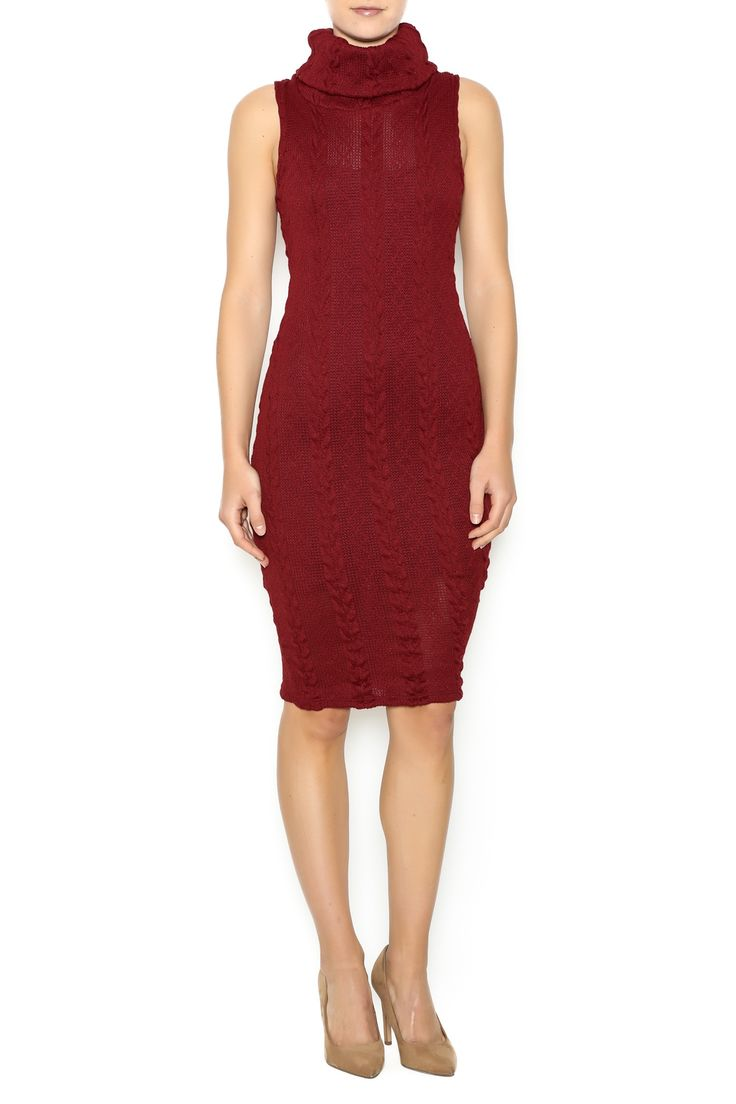 Cable knit sleeveless sweater dress with a turtleneck and knee hemline.