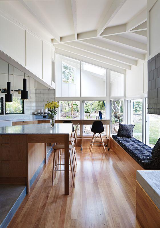 Architekti používají Blackbutt dřevo na podlahy a Whisper bílou barvou podle Dulux po celém interiéru.  A110 ruční granát přívěsek lampy, Alvar Aalto pro Artek, visí nad bílého carrarského mramoru deskou ostrova.
