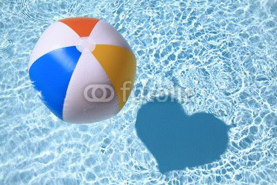 Beach Ball on the swimming Pool with heart shaped shadow