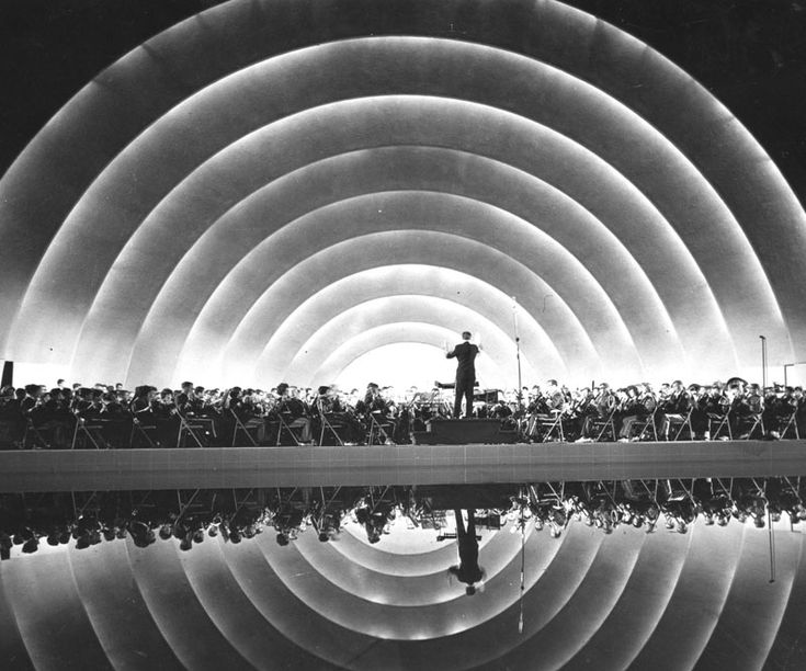 "1968 View of the Hollywood Bowl where an orchestra plays their music on stage. Photo caption reads: ""Reflection of the past: Where now there are box seats once lay a pool that gave the bowl visual resonance in addition to the aural kind."""