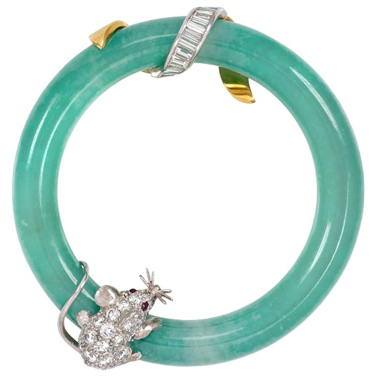 1950s Cartier Jadeite Ring Brooch with Diamond Mouse. A circular blue-green jadeite brooch embellished with a diamond mouse with ruby eyes and a scrolling baguette diamond ribbon, in 18k gold and platinum. Cartier, #6070597.