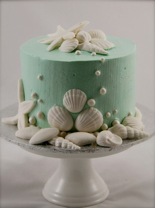 beautiful simple green beach wedding cake with candy shells