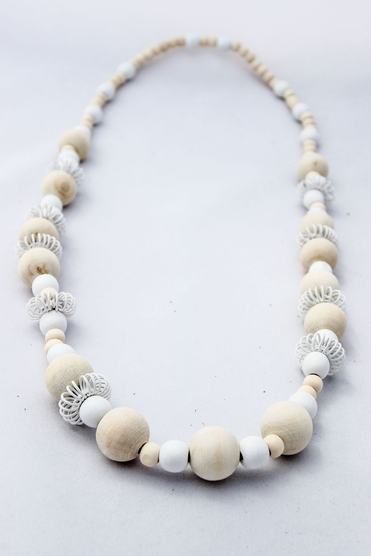 Beautiful Natural and White Asymmetrical Necklace consisting of different size natural and white beads separated by white wire pincushions. Sold @ www.wave2africa.com