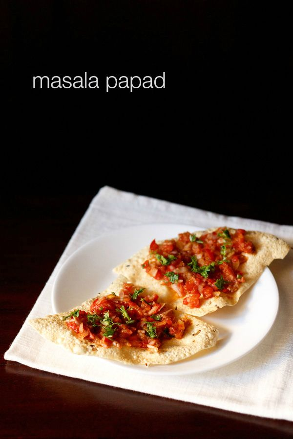 masala papad - a starter snack of crisp fried papads topped with a masala filling of onions, tomatoes and spices.