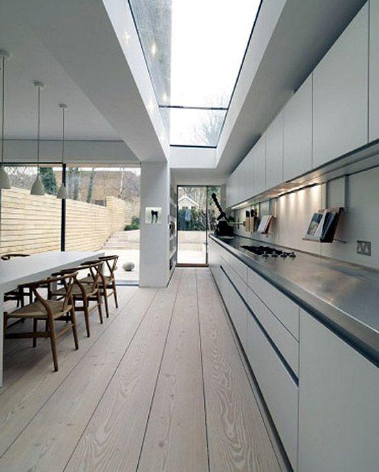 lange keukenwand wordt nog verlengd door de vloer + leuke kookboekhouders haken elegant over rand van achterwand met subtiele uitsparing