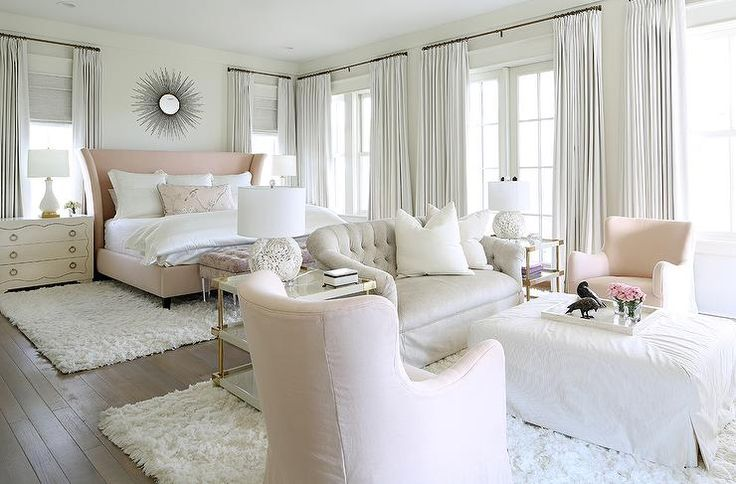 Pink and gray bedroom sitting area is filled with a light gray velvet tufted settee flanked by Bernhardt Brielle Large End Tables and white flower lamps.