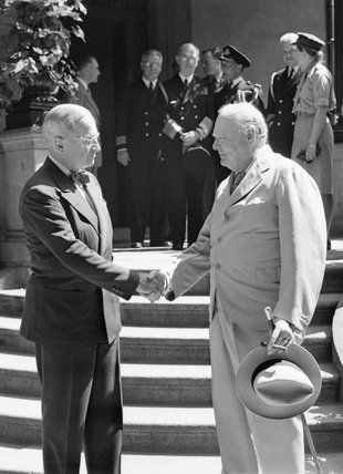 President Harry Truman and Winston Churchill shake hands on the steps of Truman's residence during the Potsdam conference, 16 July 1945., Lo...