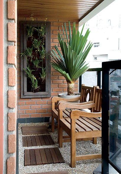 Mesmo pequena, a varanda tem espaço para as poltronas de madeira de demolição e o vaso de granilite com pândano. O painel com orquídeas-chuva-de-ouro aumenta a presença de plantas. Projeto da paisagista Paula Magaldi