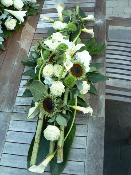 yes, you can have a white wedding in the fall! check out this beautiful arrangement with white roses and calla lilies mixed with sunflowers (yellow petals removed to reveal the green sepals)