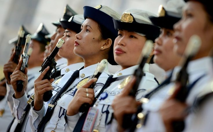 Female security guards hold up their firearms with taped barrels prior to New Year's Eve celebrations in Manila. The taping is supposed to e...